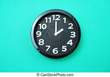 black round clock showing two o'clock on blue background