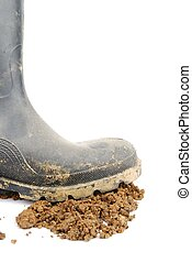 Black rubber boot and soil on white - one muddy farmer boot...