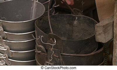 Black rubber buckets close to silvery metallic buckets - A...