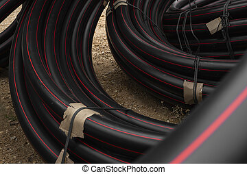 Black rubber or plastic pipes with a red lines as a construction material and equipment at building site. Using as a water pipe.