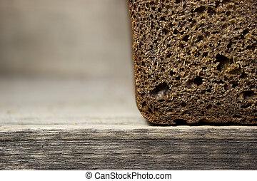 Black rye bread on wooden background.