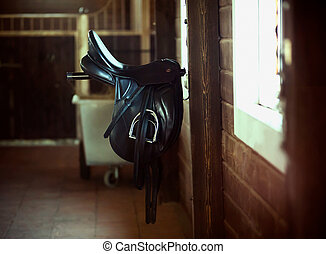 Black saddle - Saddle is hanging inside the horse stable
