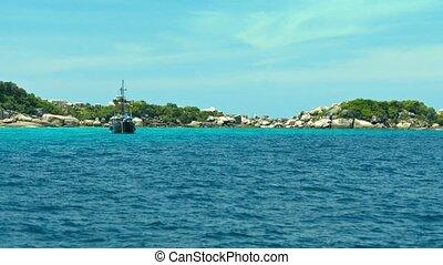 Black Sail Boat at Anchor off a Rocky, Tropical Beach