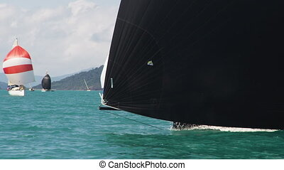 Black sailboat coming through - A black sailboat coming...