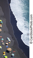 Black sand beach abstract, shot from above