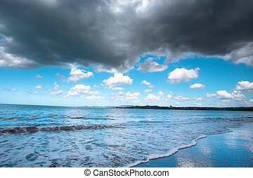 Dark storm clouds over Beautiful black sand beach and ocean at shoreline seen from Puerto Rico