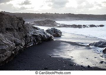 Black sand beach in Lanzarote on sunset.