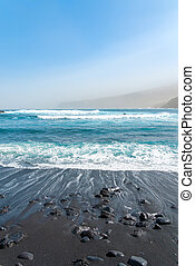 Black sand beach with rocks. Oceanic waves crashing. Blue sky and mountains in a fog. Tenerife, Spain