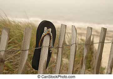 A single black sandal left hanging on a fence at the beach at the end of summer