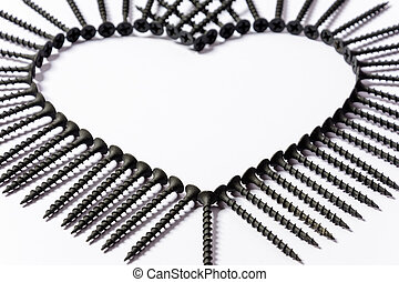 Black screws laid out in the shape of a heart on a white background