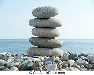 Black sea and pyramid of pebbles