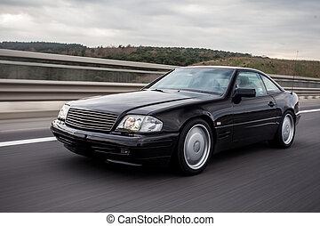 Black sedan car high speed drive on the road
