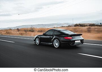 Black sedan driving on the highway