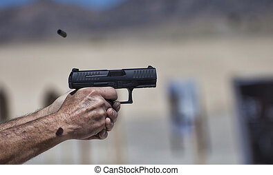 Black semi auto handgun - Pair of hands holding a handgun as...