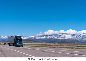 Black semi truck on the freeway