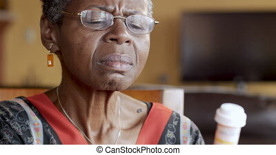 Black senior woman putting on glasses to read her prescription bottle