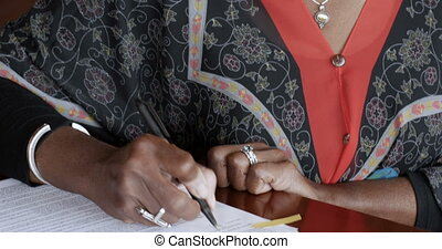 Black senior woman signing her name on legal paperwork with...