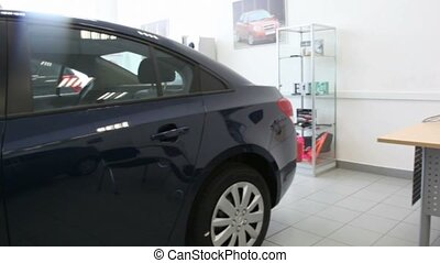 Black shiny new car is in an office car salon close to a...