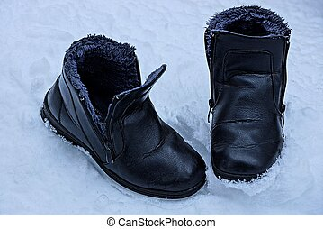 black shoes with fur stand on white snow