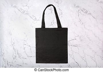 Black shopping bag on marble background with natural pattern...