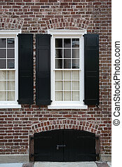 black shutters on brick wall