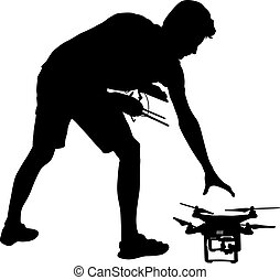 Black silhouette of a man operates unmanned quadcopter...