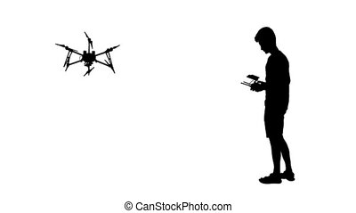 Black silhouette of a man operates unmanned quadcopter,...