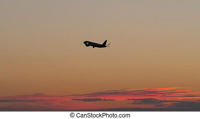 Black silhouette of flying airplane in the evening sky