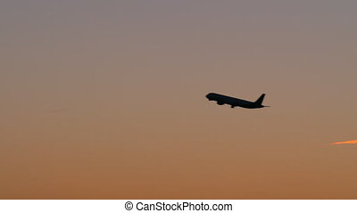 Black silhouette of plane flying in evening sky - Slow...