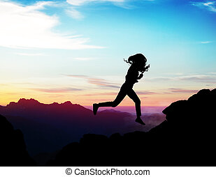 Black silhouette of woman running forward on the rock.