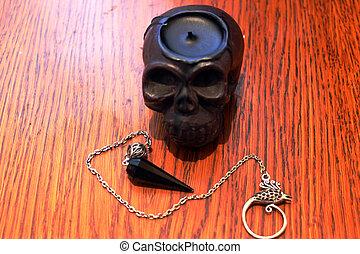 black skull candle and pendulum
