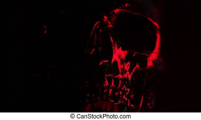 Black skull head rotates on dark background with bloody red...