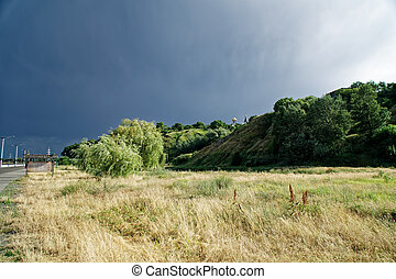 Black sky over the green hill, before storm