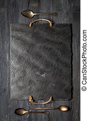 Black slate plate and three vintage spoons on wooden board. Top view, copy space, vertical composition