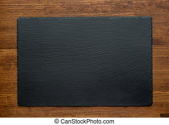 Black slate stone on wooden background, top view
