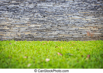 Black slate wall and green grass in garden
