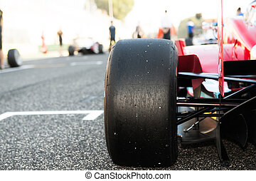 Black slick motorspor tire close up, red car on starting grid with out of focus background
