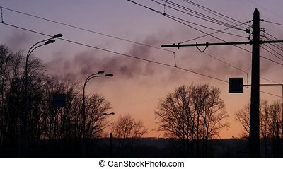 black smoke from factory pipes on a sunset background in the city. Air pollution concept.