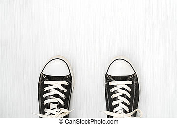 Black sneakers on a wooden background