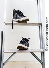 black sneakers on Aluminium ladder with gray wall dirty
