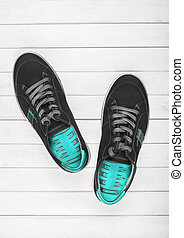 Black sneakers with blue lining on a white wooden background