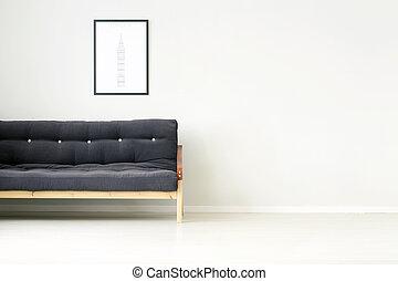 Black sofa against empty wall