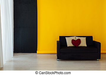 black sofa in the interior of the room with a yellow background