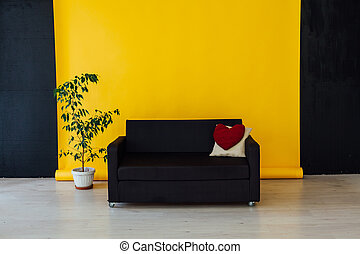 black sofa with pillows in the interior of the yellow room