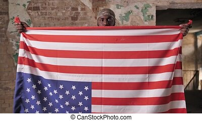 African american army man in camouflage bandana holding USA flag upside down protesting against racism. Bearded dark-skinned military male using US flag to transmit distress signal in this way