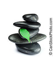 black spa stones   with green leaf and a drop of water isolated on white