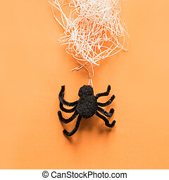 Black spider and web on orange. View from above. Minimal Halloween party decor.