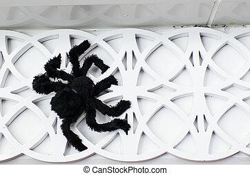 Black spider on white wall decoration.