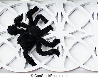 Black spider on white wall decoration.
