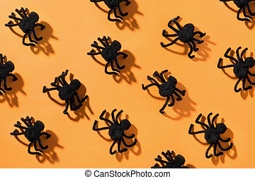 Black spiders on orange. View from above. Open composition. Halloween party pattern.